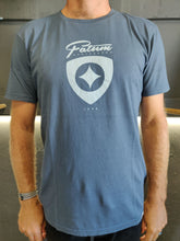 Load image into Gallery viewer, Fatum Plectrum Tee in Blue. Model is wearing an L and is 186cm and 86kg.