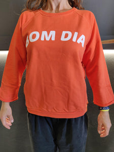 Fatum Bom Dia in Orange. Model is wearing an S and is 164cm tall and 50kgs.