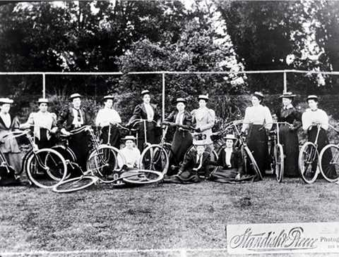 A black and white photo showing a line of women with bicycles.