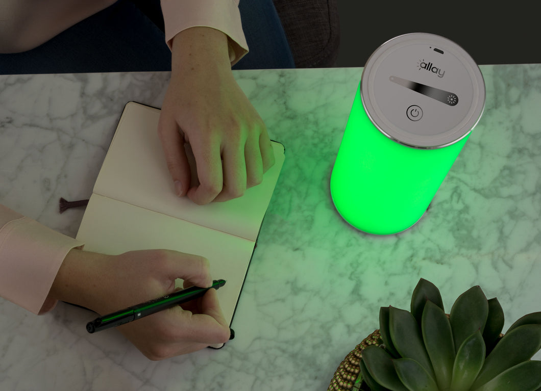Writing in a journal using the Allay Lamp