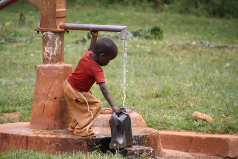African child gathering water from a water well with pump.