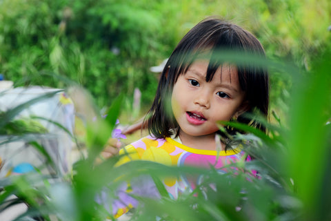 Little Asian girl in tropical foilage