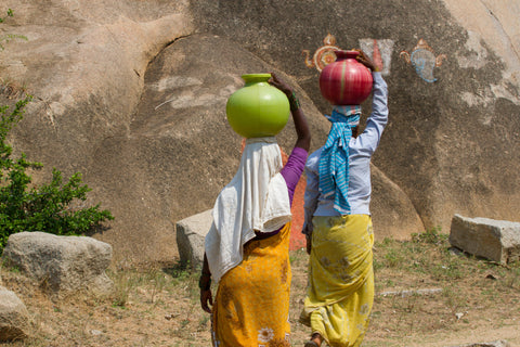 African women carrying water jugs on their heads.