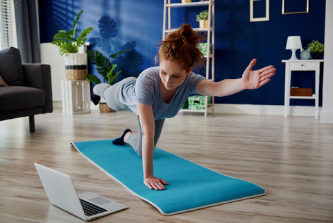 Woman doing yoga pose while looking at laptop