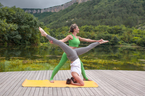 Two women doing yoga outdoors together