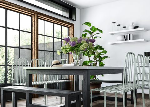 INDUSTRIAL LOOKING DINING ROOM WITH BIG FLOWER ARRANGEMENT ON THE TABLE
