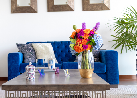 LIVING ROOM WITH BLUE SOFA CENTER TABLE AND A FLOWER ARRANGEMENT