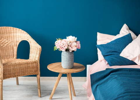 BLUE ROOM WITH A CHAIR AND NIGHTSTAND WITH A FLOWER ON TOP