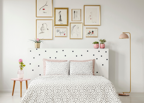 WHITE ROOM WITH DOUBLE BED FRAMES ON THE WALL AND SMALL PLANTS