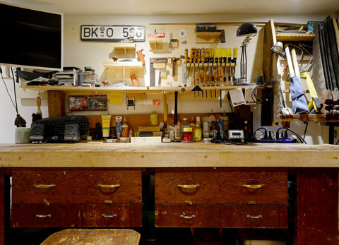 An old school woodworking workbench with tools hung on the wall. This is where all Beck + Adele speakers are made.