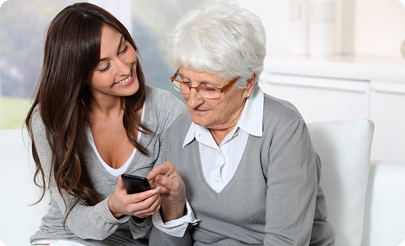 elderly woman and daughter on couch looking at phone