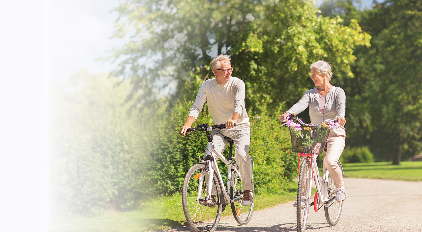 older man happily riding a bycicle, balancing with his legs out. His wife can be seen behind smiling, but out of focus