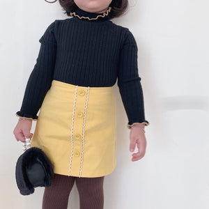 Black sweater + yellow skirt