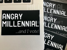 "Load image into Gallery viewer, A black rectangular vinyl sticker that reads ""Angry Millennial"" in large bold font with small, italicized font on the bottom right corner that reads, ""…and I vote!"" All lettering is in white."