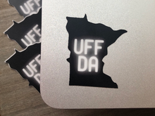 "Load image into Gallery viewer, mage: Black die-cut sticker in the shape of the U.S. state of Minnesota. The word ""UFFDA"" is in the center of the sticker in glowing, white lettering"