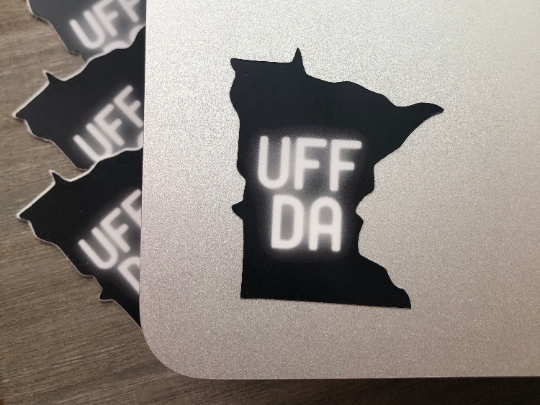"mage: Black die-cut sticker in the shape of the U.S. state of Minnesota. The word ""UFFDA"" is in the center of the sticker in glowing, white lettering"