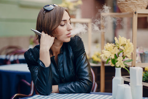Woman vaping at a cafe enjoying flowers in a vase on the table