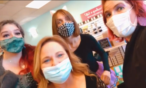 A bunch of ladies in masks having fun at work