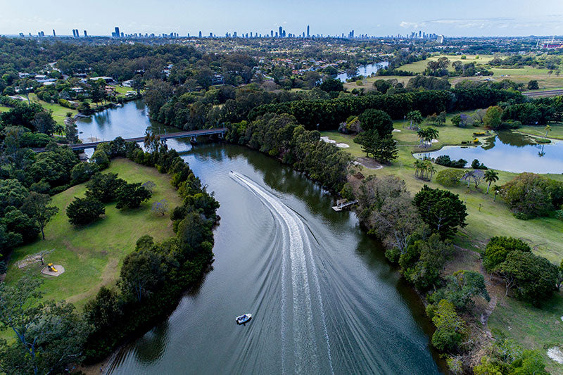 aerial imagery by my drones boat cruising on river behind gold coast high rise buildings next to golf course droneography