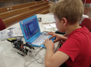 A boy is using robotics kit to build and code a robot to learn robotics and STEM