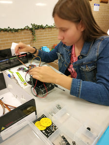 Girl is building a robot at online robotics class for kids