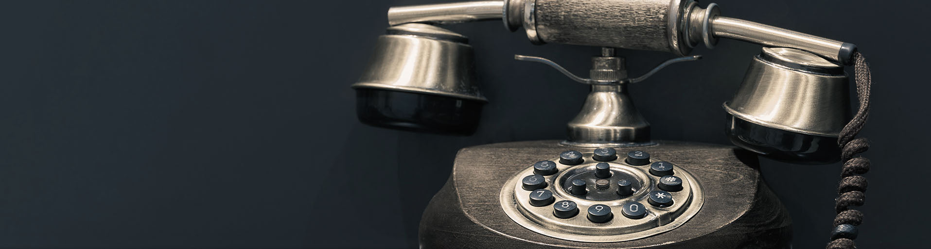 Black old telephone in front of dark background