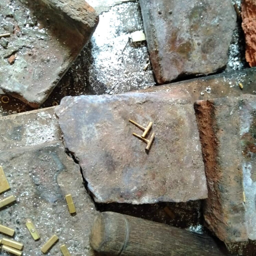 Cornerstone earrings on bricks with pieces and mallet. Delicate stick post earrings handmade of brass plated with 14K gold. .13 inches by .38 inches. Made in Kibera, Kenya. These will be your favorite go to daily earrings.