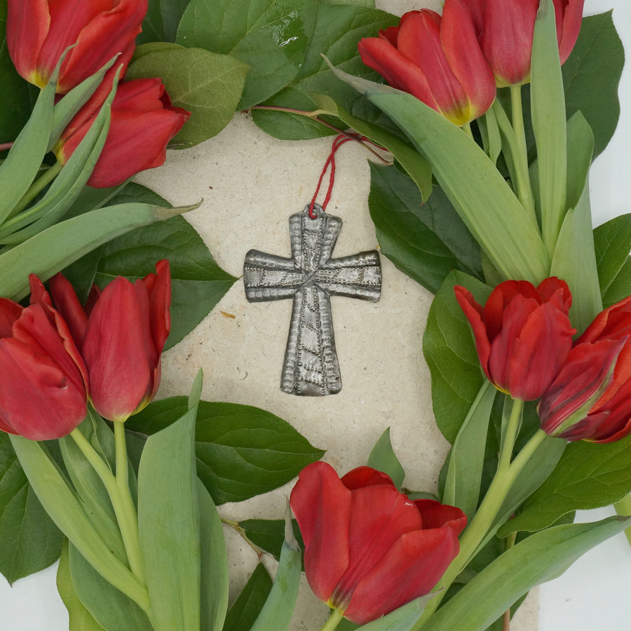 The Haitian Metal Cross is beautifully and intricately handcrafted in Haiti. The cross makes the perfect gift. Each cross comes pre-wrapped and ready to give with a gift tag.  3.25 inches by 2.5 inches. Handmade from up-cycled steel drums. Circled by fresh red tulips.