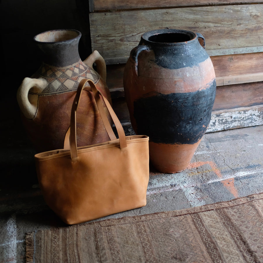 Stylish tote that holds your carry all needs.  Made of Ethiopian leather.  Interior zippered pocket and leather strap with snaps to change the look.  Leather/metal key clasp included.  Flat bottom to sit easily.