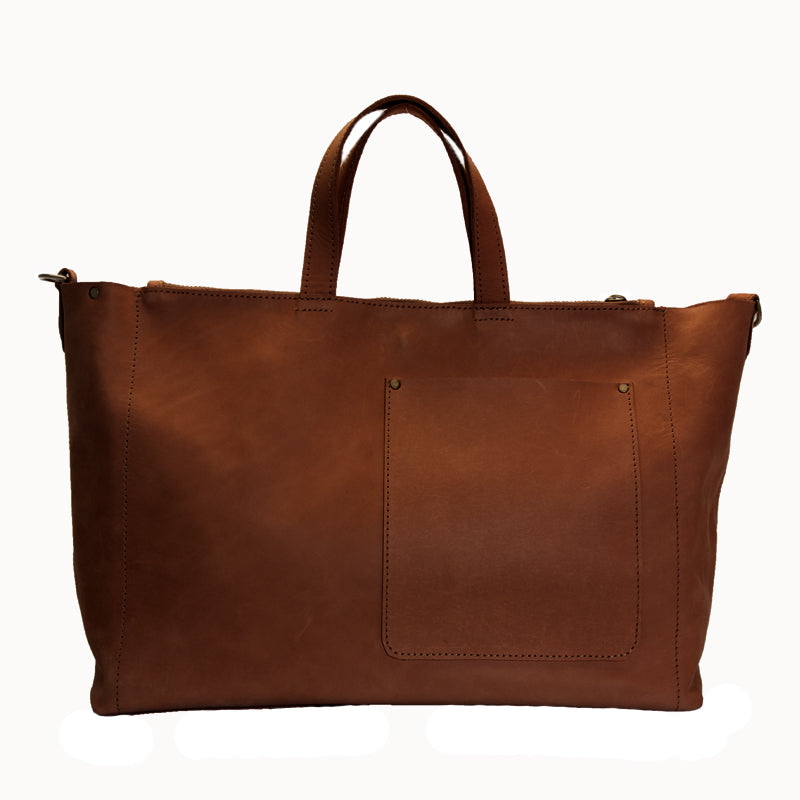 Stylishly elegant, flexible leather bag made of soft Ethiopian leather, perfect for everyday use or travel. Large, zippered compartments with outside pocket and key chain hook. 18 inches wide, 10 inches tall and 6 inches deep. Removable 1 inch wide strap, magnetic closure. Satchel color is cognac