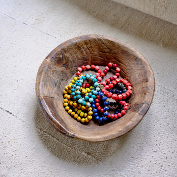 Wooden bowl of colorful, glazed ceramic bead bracelets. Handmade in Haiti