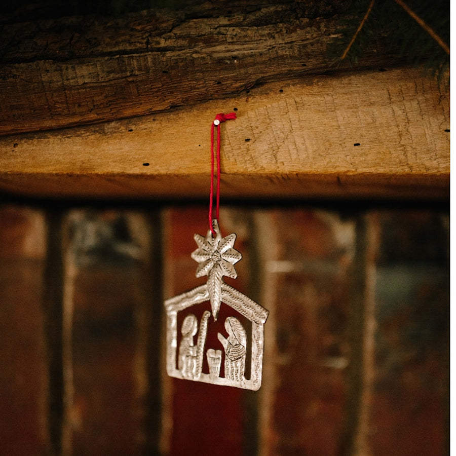The Nativity Ornament, hanging from a nail on rustic wood, displays the Christmas Story through the delicate artwork, hand-hammered by artisans in Haiti. Ornament comes pre-wrapped with a gift tag and red string hanger. 3.25 by 2.5 inches. Handmade from up-cycled steel drums