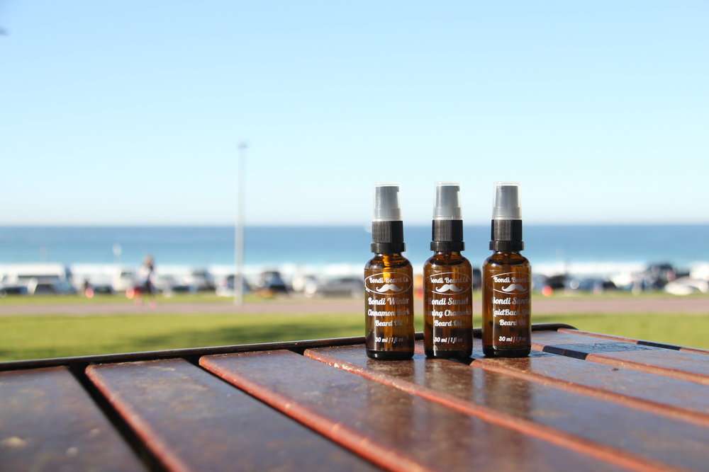 Image of 3 dark brown Bondi Beard Co. spray bottles placed on table with beach in background