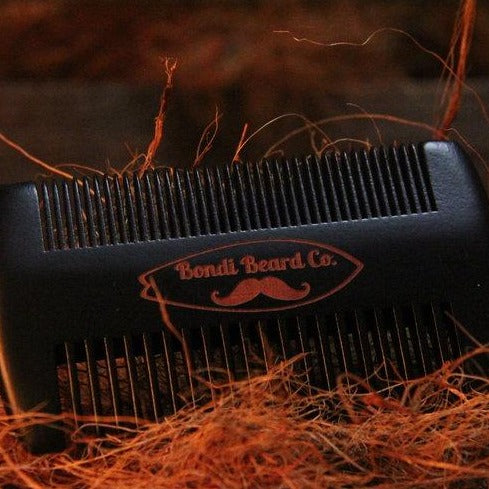image of two-sided black comb with Bondi Beard Co. branding sitting on Copper hued fibres