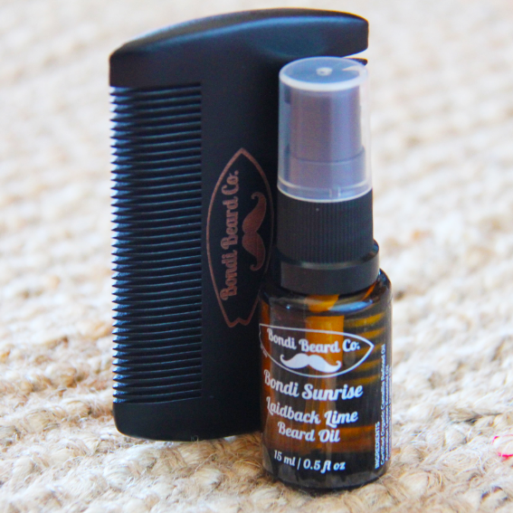 image of small atomising vial of beard oil with a black two-sided comb, both with Bondi Beard Co. branding and sitting on a fibrous mat