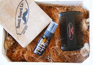 image of wooden crate with a small atomising vial of beard oil, a black 2-sided comb, and hessian bag, all with Bondi Beard Co. branding, sitting atop copper hued fibres