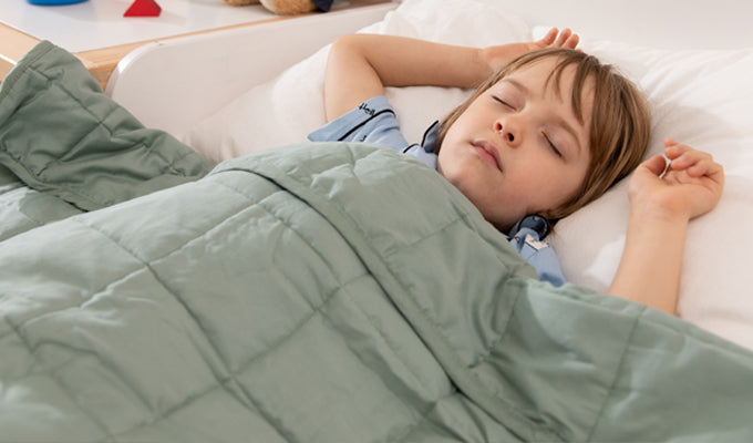 Boy Sleeping With A Green YNM Weighted Blanket
