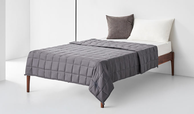 Bed With Dark Grey YNM Weighted Blanket On It With White Background