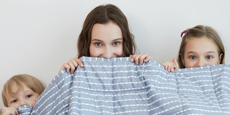 Mother, Son and Daughter Hiding Behind A Striped YNM Weighted Blanket