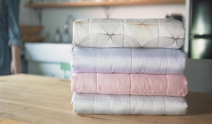 Pile Of YNM Weighted Blankets On A Table
