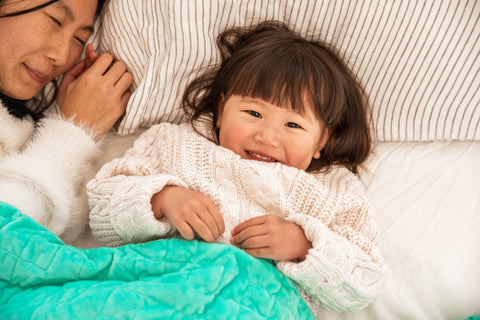 Child lying in bed with weighted blanket
