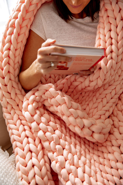 Women comfortably wrapped in knitted weighted banket
