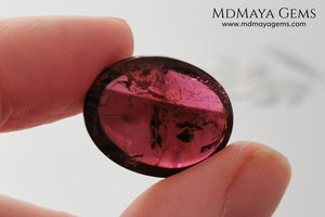 Large tourmaline rubellite, 16.08 ct, oval cabochon cut. This beautiful natural gem features two shades of color, one darker than the other. Although it has inclusions, it will be beautiful once mounted on any piece of jewelry you can imagine. And the best its price. $15 per carat.
