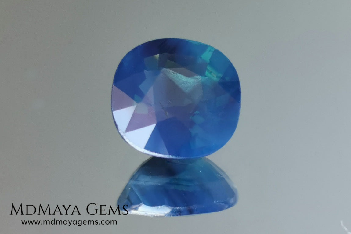 Untreated greenish blue Sapphire 3.61 ct. Cushion cut.  natural untreated blue sapphire has a large green component inside, under natural light you can see a dull and translucent blue sapphire, although under incandescent light everything changes, this sapphire shines from all sides and a bright green color is seen throughout the interior. It is a gem only for the very daring, with an extra: its price (certificate included).