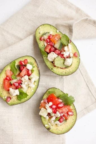 An avocado stuffed with feta cheese, grapefruit chunks, cilantro leaves, and pomegranate seeds makes a substantial snack.