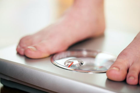 Female feet on a scale, a woman weighing herself