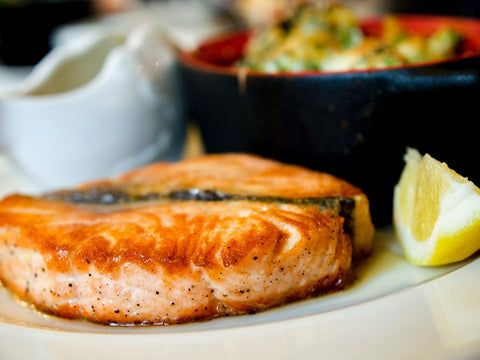A fillet of salmon on a plate with lemon and salad