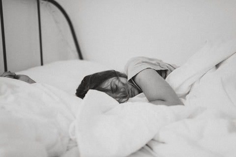 A woman sleeping in bed, feeling restless