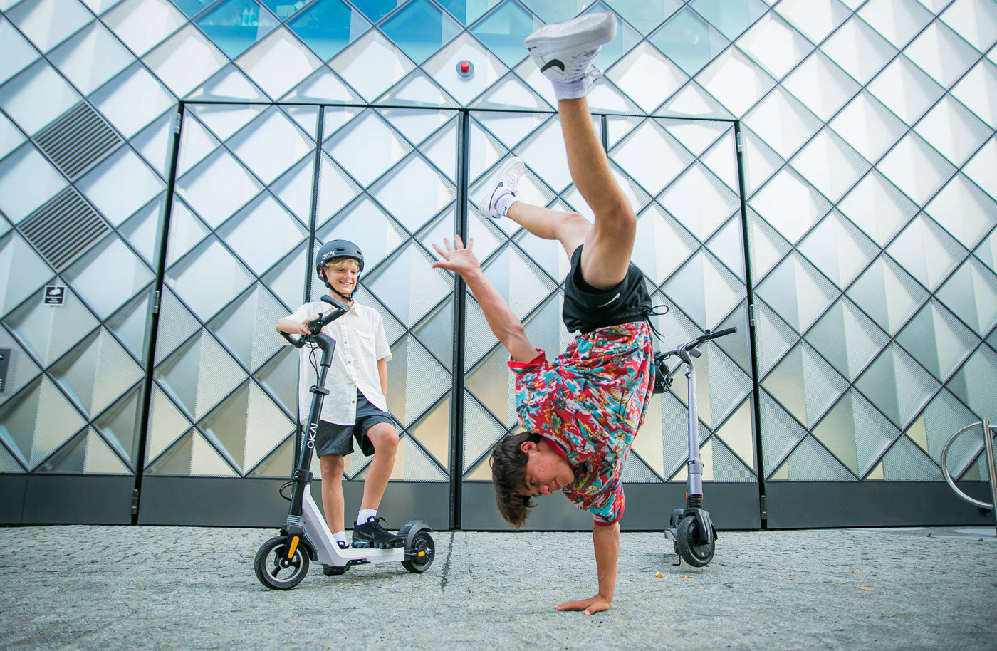 Okai-Electric-Scooter-&-Electric-Bike-Manufacturer-ES50-Kid-performing-a-handstand-in-front-of-the-electric-scooter