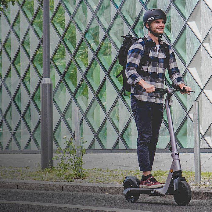 Okai-Electric-Scooter-&-Electric-Bike-Manufacturer-ES500-Electric-Scooter-Rider-in-front-of-Berlin-tech-museum